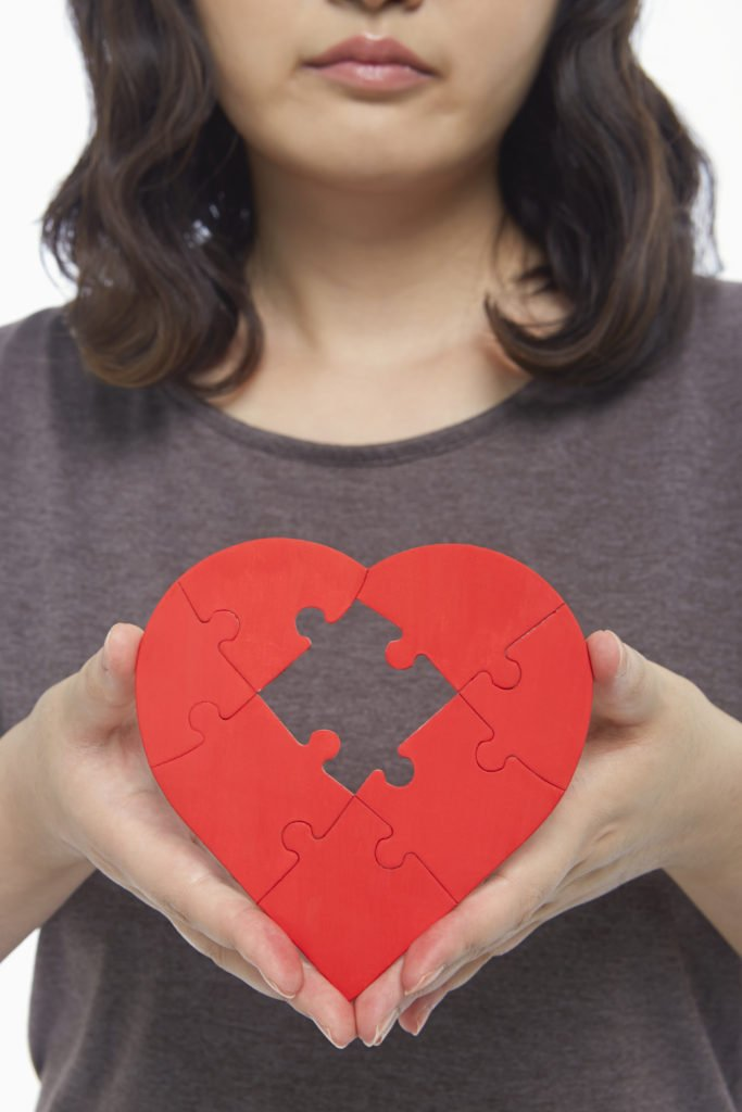 Sad woman holding up a red heart shape with a missing puzzle piece, she has lost part of herself in an abusive relationship or relationship with a narcissist
