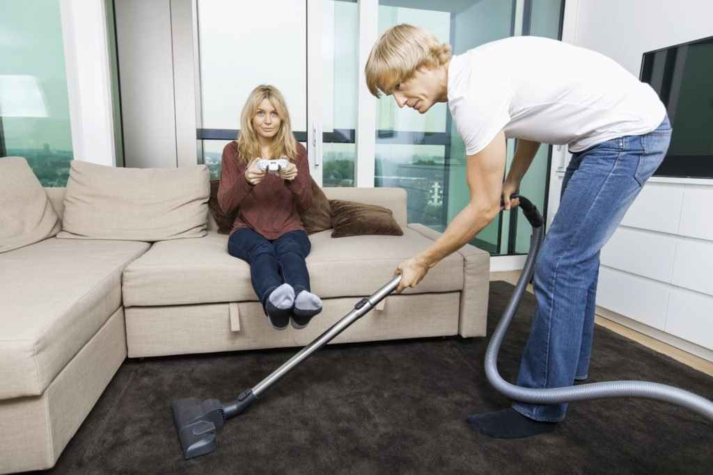 Man vacuuming while woman play video game in living room at home | Holiday for overworked single moms who need a break | National No Housework Day | 4 ways to celebrate