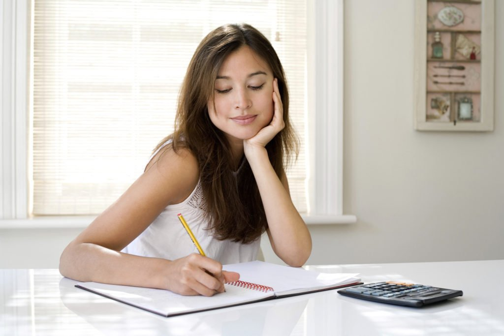 woman working on maximizing her finances checking investments cleaning up credit budget spending plan tips and tricks to maximize