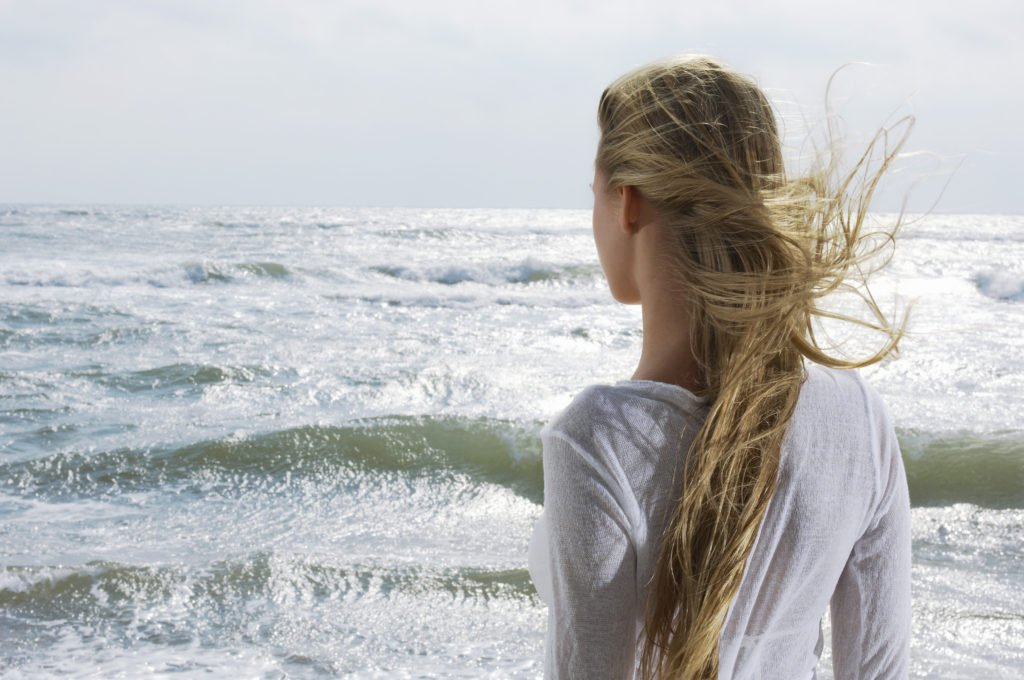 Young Woman Looking at Ocean wondering who she is after losing herself in a relationship or tragedy of life