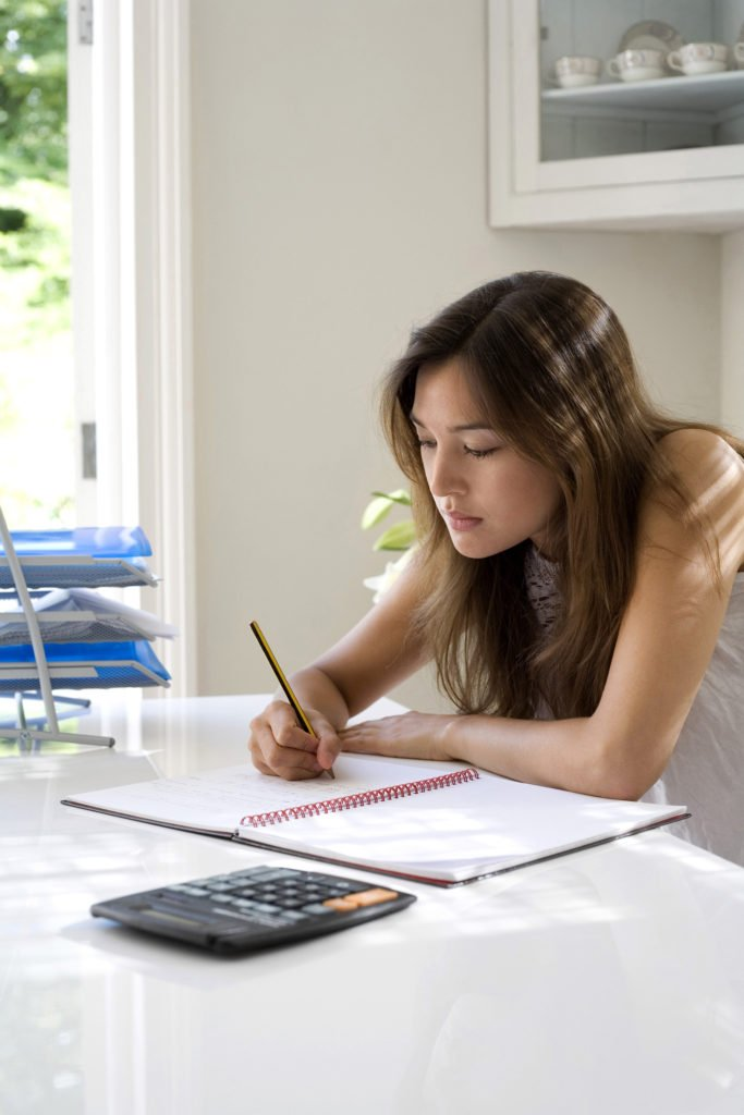woman checking over her monthly expenses to reduce them so she can save more each month and find new methods to pay down debts