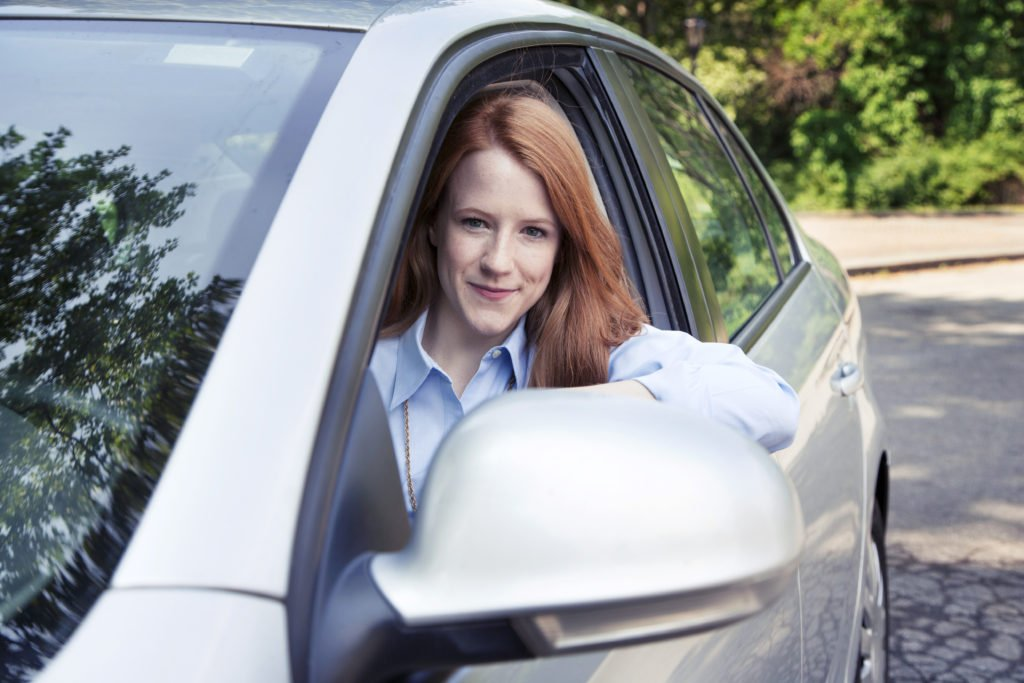 Teen girl driving her car, conducting a simple safety check to earn a full ride scholarship to college.