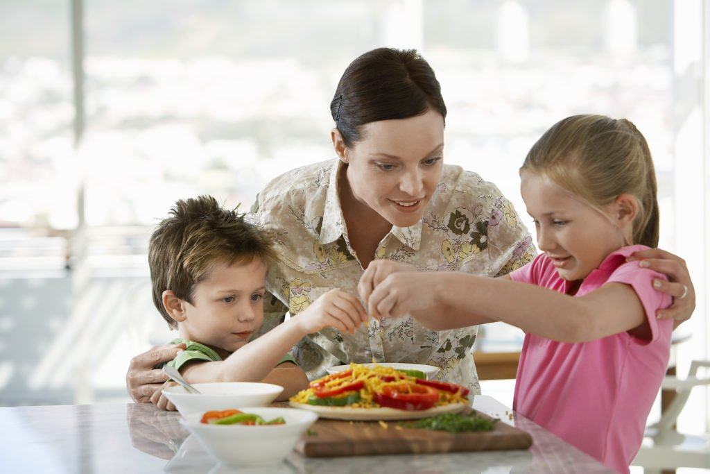 Mother Helping Children Prepare a Meal to avoid eating in restaurants, stop eating out to reduce costs, cut spending by eating at home