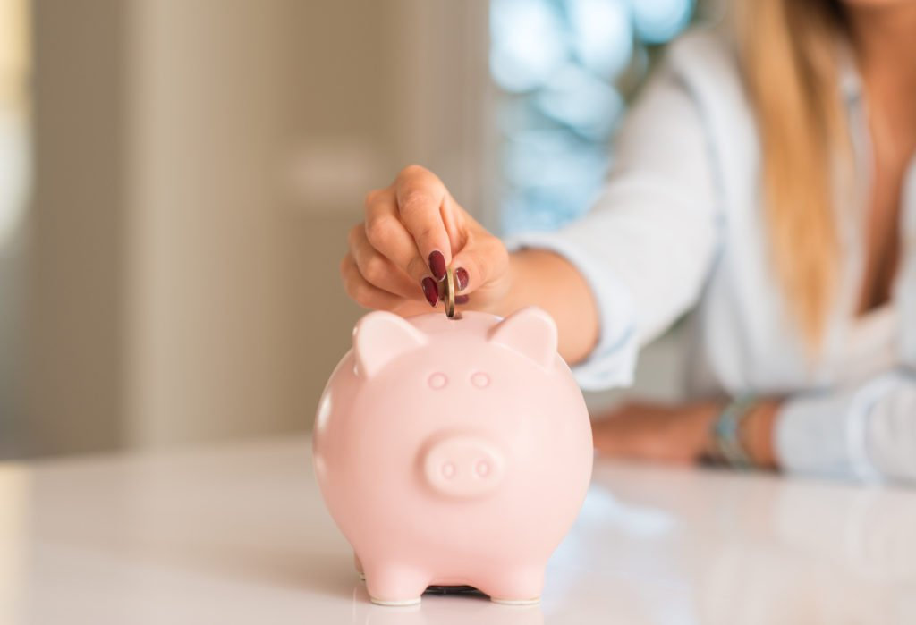 Beautiful young woman hands holding a coin investing in to a piggy bank at home. Earn more interest on your savings, savings account earnings, build your savings, start an emergency fund, get more interest now, make more on your savings, increase your savings account, find a bank with high interest, what bank has high interest