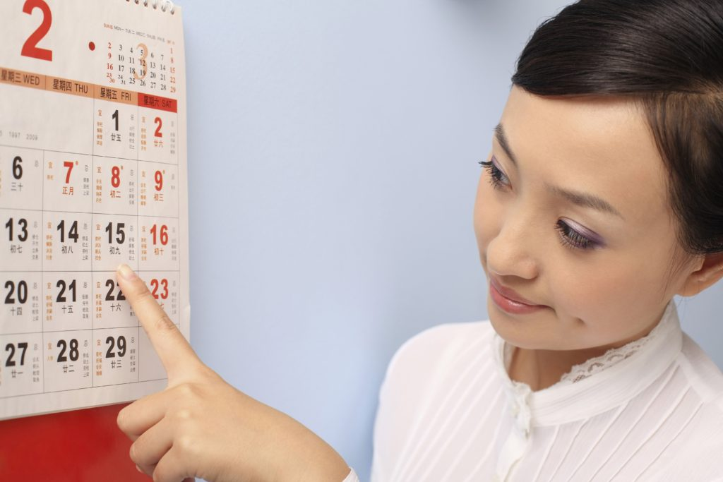 Girl viewing calendar, paying bills on time to raise her credit score.