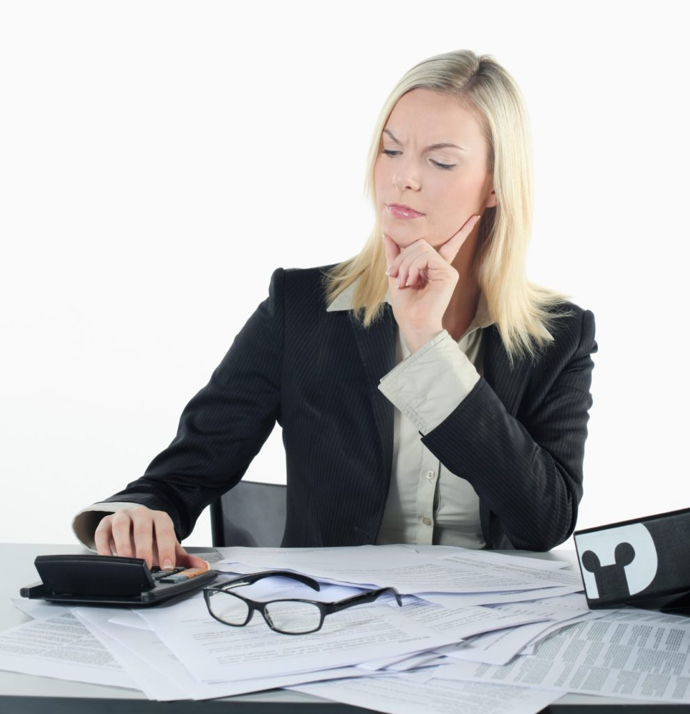 Woman working on an annual financial check up using her calculator and paperwork.