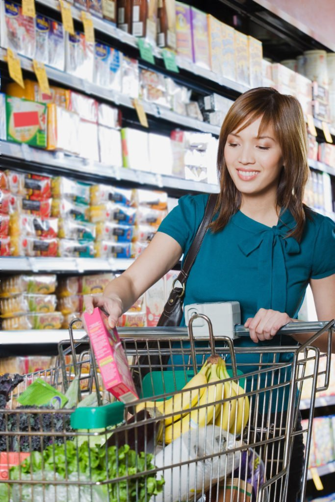 woman shopping for bargains, using coupons at the grocery store, using and app to save money on food