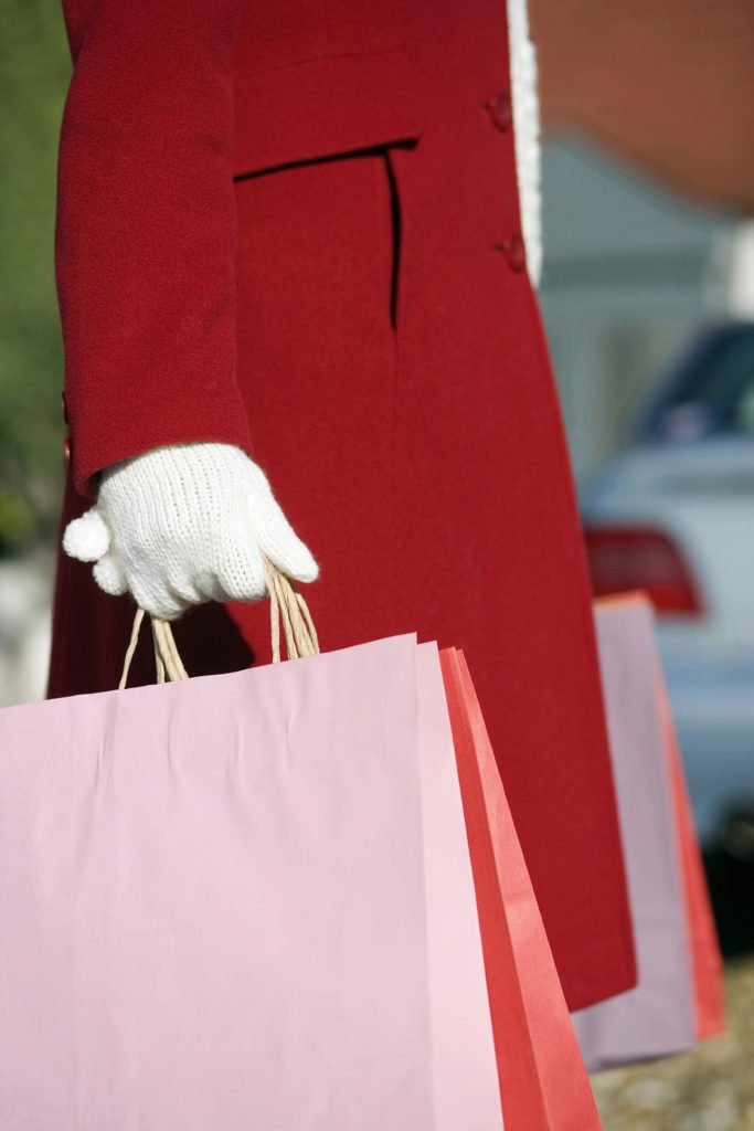 Woman in christmas coat carrying bags from holiday shopping, deciding to layaway or to put the purchases on credit