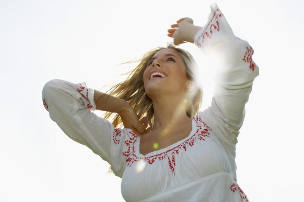 young woman enveloped in sunbeams, full of hope