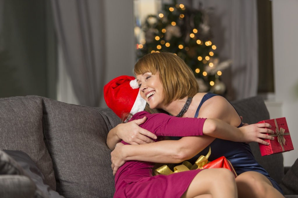 Happy daughter hugging her mother at Christmas.  Gifts don't need to cost a lot.  We can prepare for Christmas to stay out of debt.