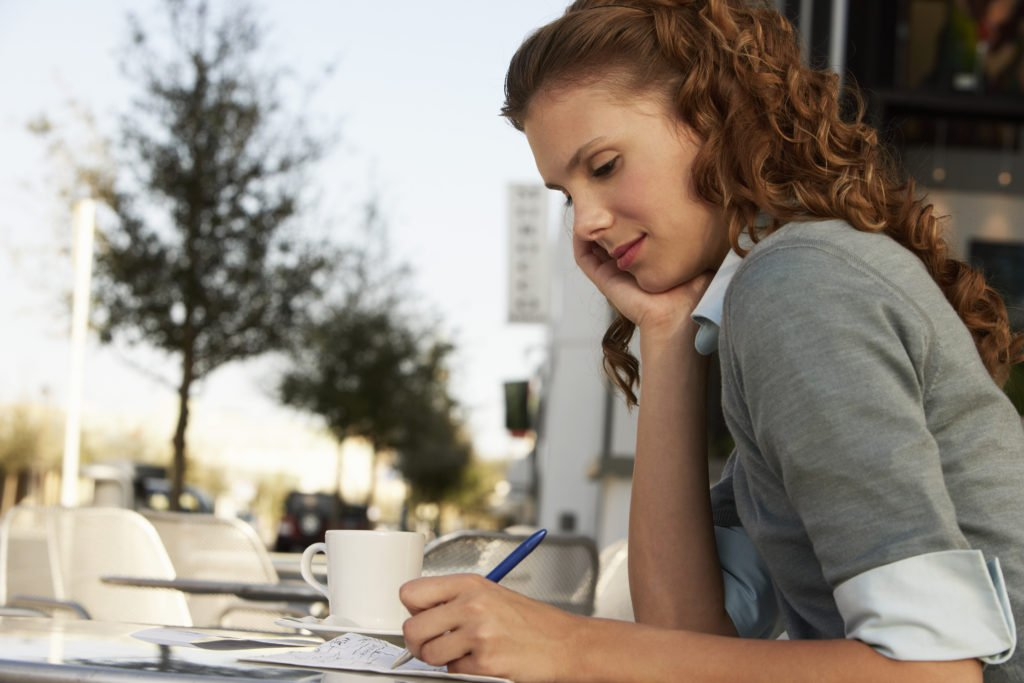 woman writing in notebook, writing down thoughts, using brain dump to overcome overwhelm, writing to overcome feelings of overwhelm, stop feeling overwhelmed