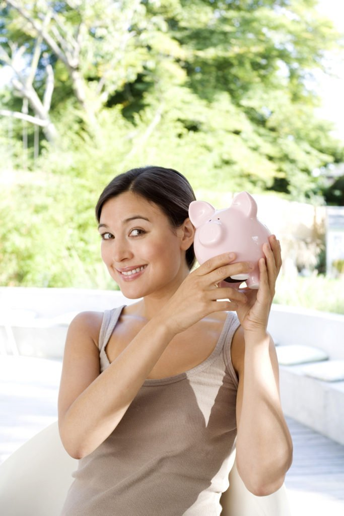 woman holding piggy bank, minimalist budget, percentage based budget, 70 20 10 budget, 10 percent savings goal, woman writing a budget, help with your budget, best budget ever