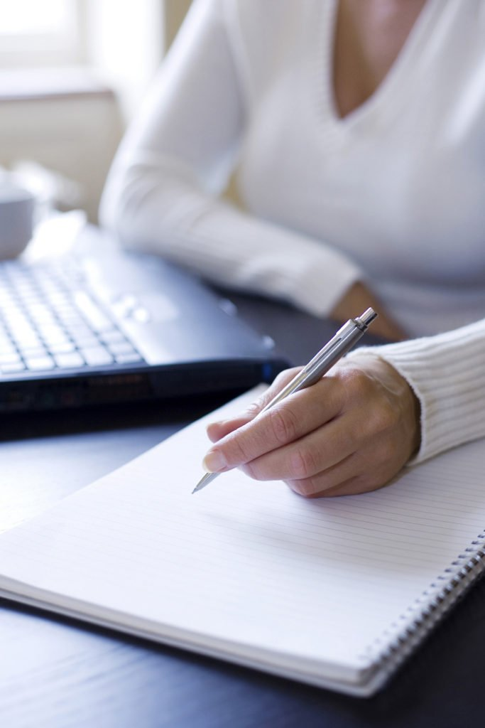 woman writing her accomplishments to build confidence and strength after leaving an abusive relationship